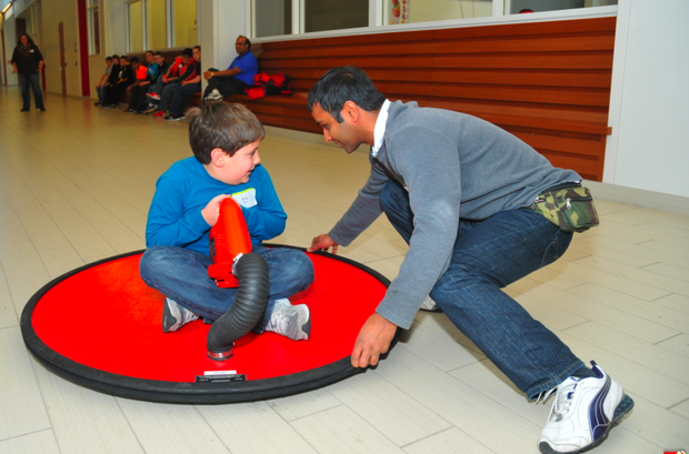 Om Goit (right), a UNL graduate student, helps a Lincoln Public Schools fifth grader ride a hover craft during Saturday Science.