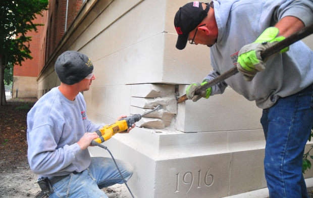 (From left) Ben Krivda and Chris Krivda of Krivda and Son Masonry work to remove the stone immediately above the Avery Hall cornerstone on May 12. A time capsule inside the cornerstone will be used as part of an October celebration in Hamilton Hall.