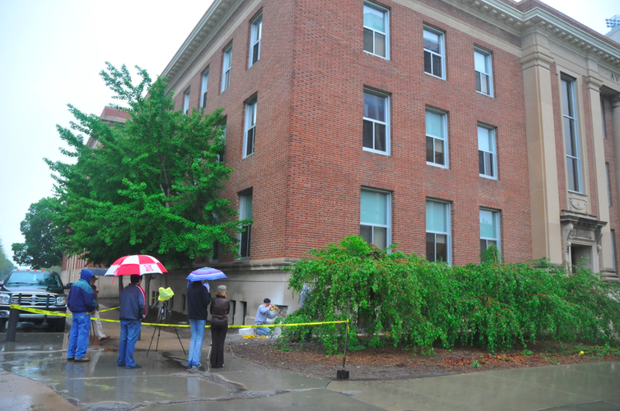 Individuals watch the removal of the Avery Hall cornerstone on May 12.