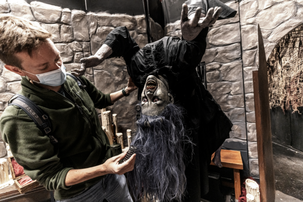 Man adjusting hair on haunted house witch figure