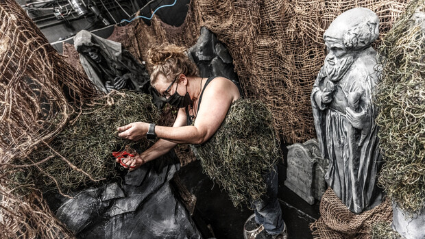 Woman working with haunted house decorations