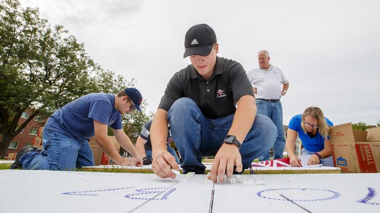 """Husker John Lang starts placing white plastic bricks on the Nebraska """"N"""" mosaic on Aug. 31."""