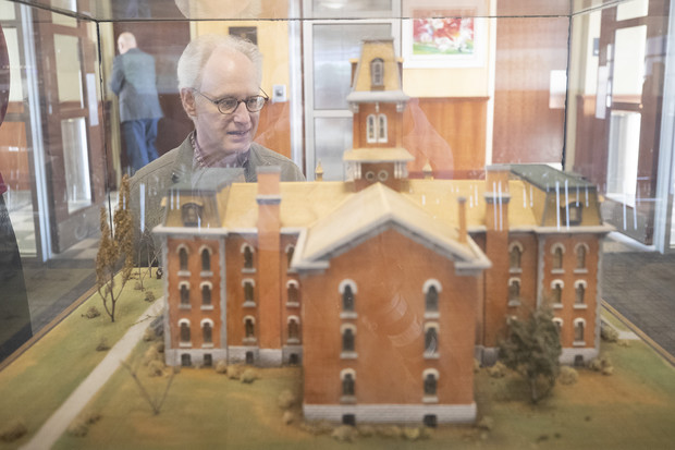 Mark Griep, associate professor of chemistry, examines a model of University Hall. The model, used by NET to create a virtual reality tour of the university's first building, was presented as a gift of the class of 1897.