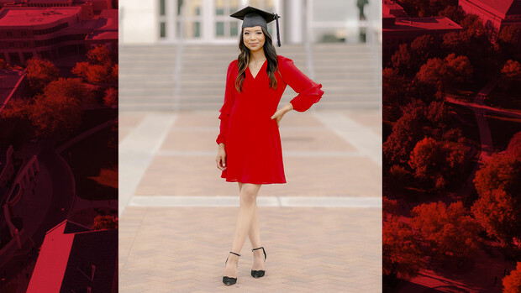 Carolina Saquiche Dominguez stands on bricks outside of Memorial Stadium wearing her mortar board.