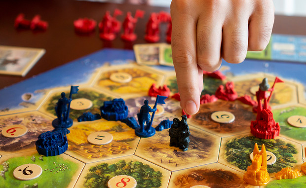 Players scramble an area in the game Settlers of Catan to earn resources and score points.
