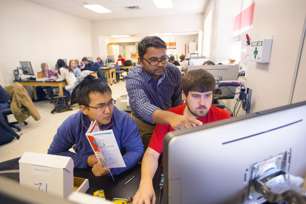 Nebraska researcher Santosh Pitla (center) assists students with a sensor-building project. Pitla is leading a new research project that will update techniques used to test tractors.