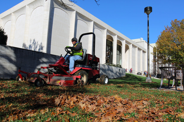 Tim Herron, a landscape assistant with landscape services, mulches leaves into the grass on the east side of Sheldon Museum of Art on Nov. 8. The university recently expanded its sustainability practices by partnering with Big Red Worms on leaf recycling.