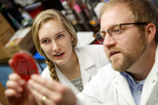 Kara Robbins looks on as Dustin Loy discusses a test sample. Robbins is using the MALDI-TOF device in research into Moraxella bacteria. The project is part of Robbins' undergraduate research project.