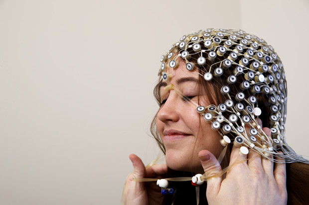 A research subject has the electroencephalogram (EEG) cap placed on her head, which maps electrical impulses in the brain.