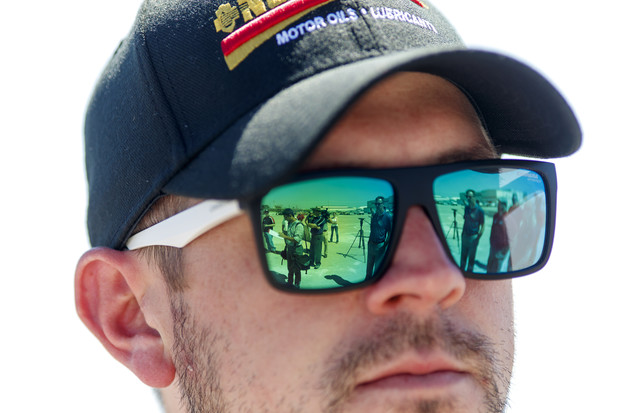 Members of the media are reflected in the sunglasses of NASCAR Xfinity Series driver Michael Annett during the tour.