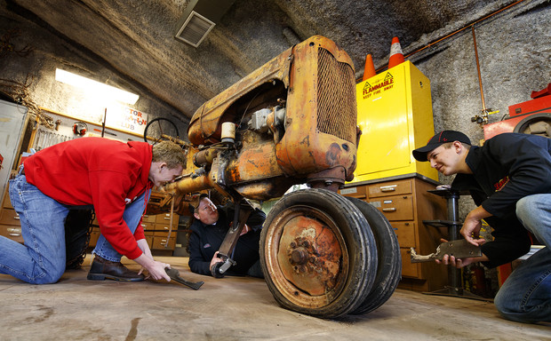 Tractor Restoration Club members (from left) Kiel Kruse, Joshua Bauer and Jaythan Scheideler work with support pieces that will be attached to the 1945 Allis Chalmers Model C so it can be moved around for restoration work. Club members are preparing the tractor for display at the Homestead National Monument of America near Beatrice.