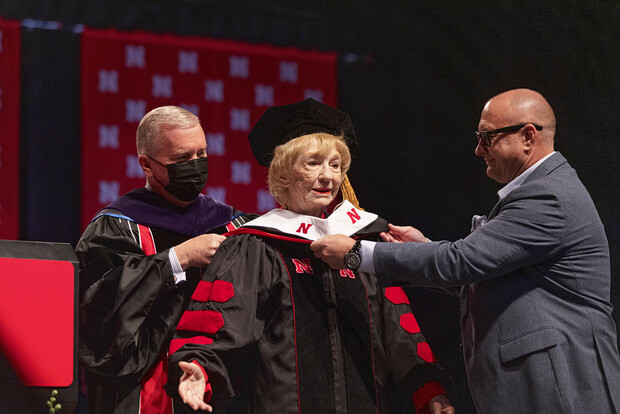 Leta Powell Drake, local television pioneer and Husker alumna, is hooded by University of Nebraska Regent Tim Clare (left) and her son, Aaron (right), during the University of Nebraska–Lincoln's undergraduate commencement ceremony Aug. 14 at Pinnacle Bank Arena. The university presented Drake with an honorary Doctor of Humane Letters during the ceremony.