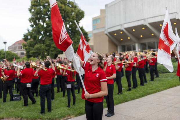 """Color guard member Haley Petri chants """"Go Big Red"""" during the Cornhusker Marching Band's warm-up concert north of Kimball Recital Hall on Aug. 20. The band then marched to Memorial Stadium for its annual exhibition before it was canceled due to lightning. The band will make its 2021 debut Sept. 4 at the stadium with pregame and halftime performances at Nebraska's football home opener against Fordham."""