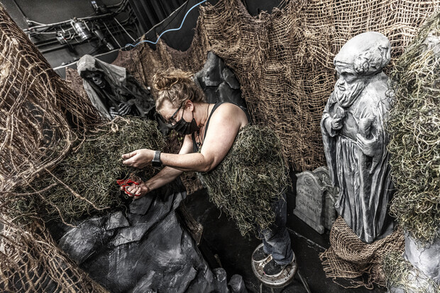 Production designer Jill Hibbard works on the scenery among the statuary.