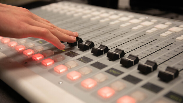 A student adjusts the board in the KRNU studio. The station is intended to allow students to get hands-on experience in the broadcasting industry.