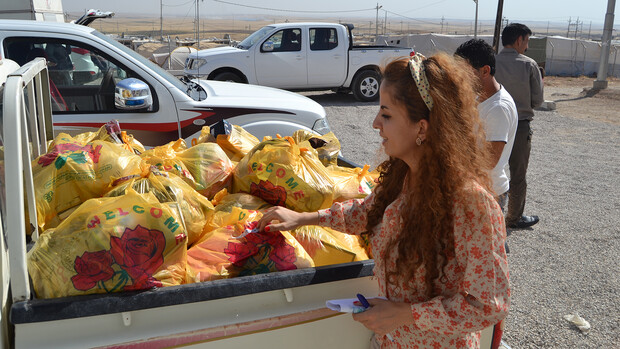 Vianne Sheikh examines bags of supplies at a refugee camp in Iraq. Sheikh was among the Yazidi who survived an ISIS-led genocide in northern Iraq.