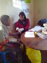 A social worker takes a sample of blood to test for HIV during a data collection in Lusaka, Zambia, in 2014.